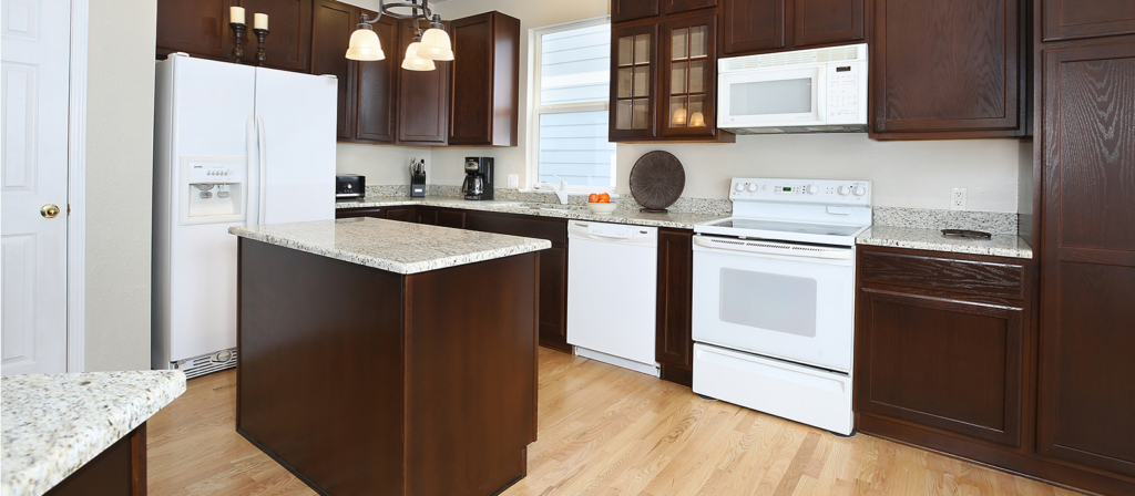N-Hance refinished kitchen with dark wood cabinets and white appliances