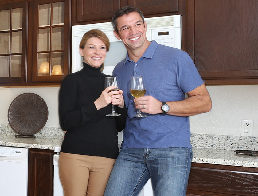 couple enjoying the new year in front of walnut cabinets in kitchen