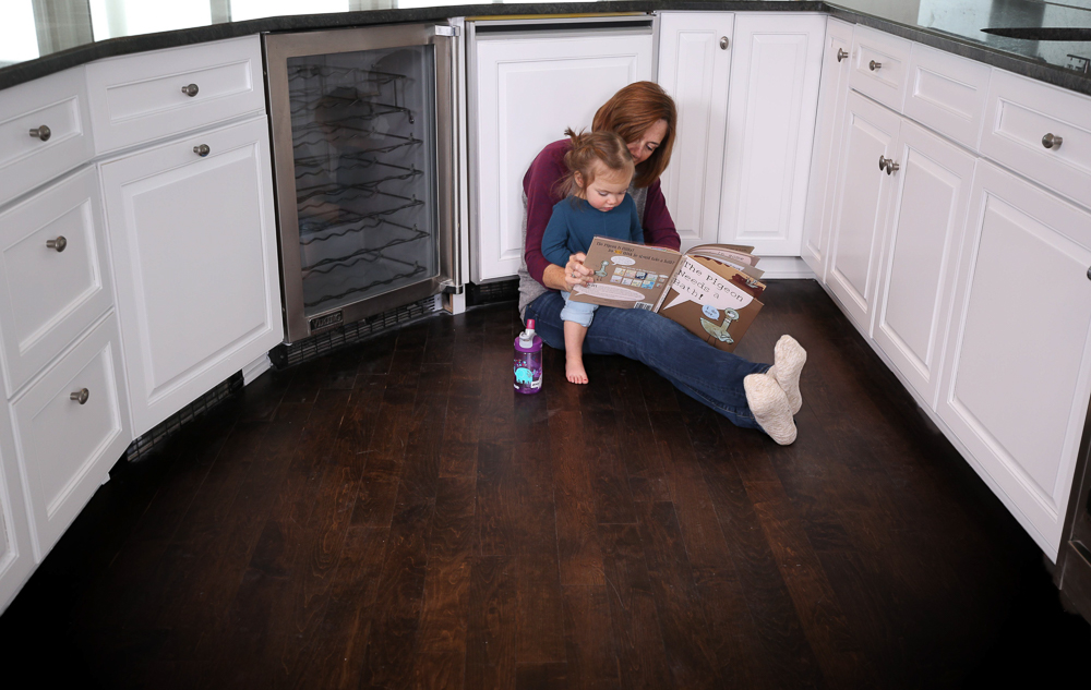 Nhance after picture of remodeled kitchen with mother reading book to her daughter while sitting on the floor