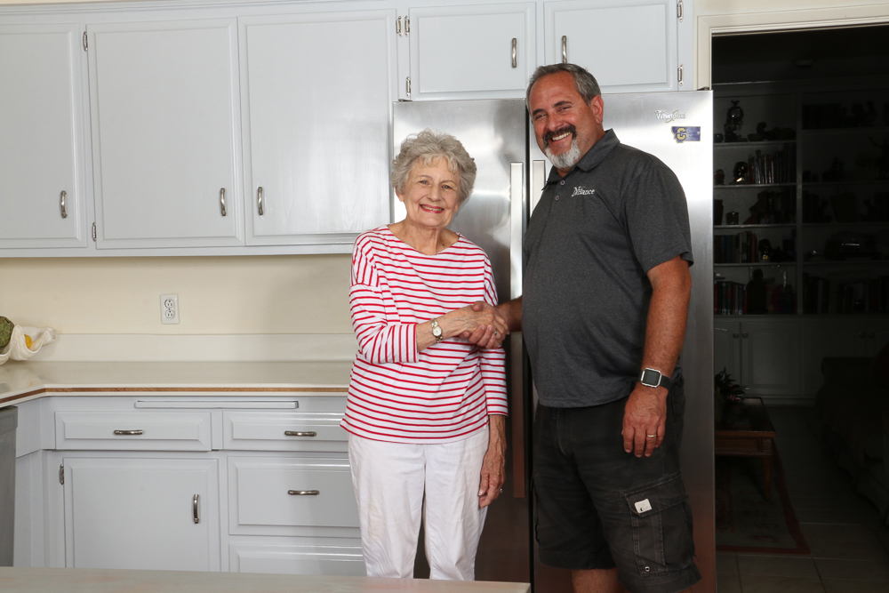 Nhance franchise owner in kitchen with happy customer