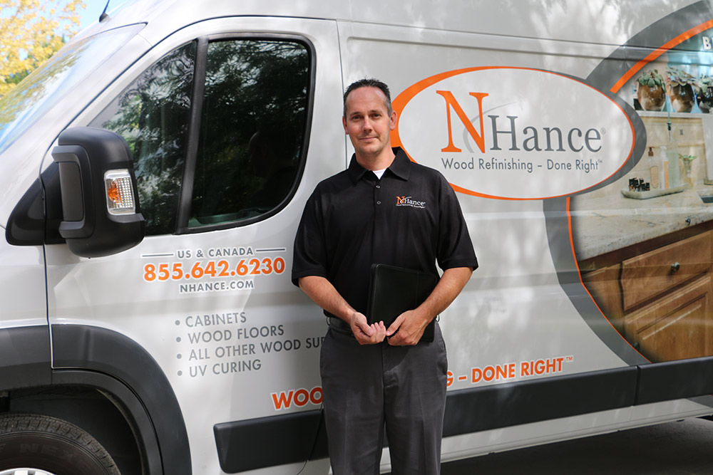 N-Hance Wood Refinishing franchise owner stands in front of his van