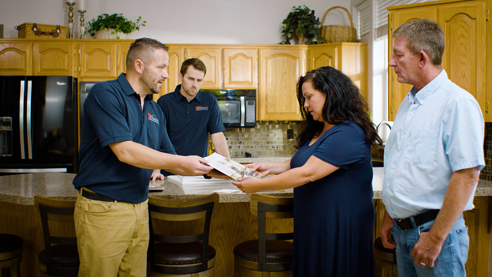N-Hance Wood Refinishing Franchise employee shows couple color swatches for kitchen cabinets