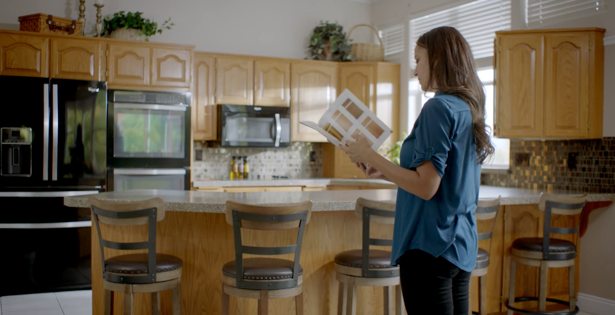 N-Hance franchise customer looks at brochure in her kitchen; home-flipping business
